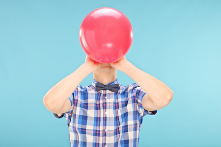 stretchy: Man blowing up a balloon on blue background