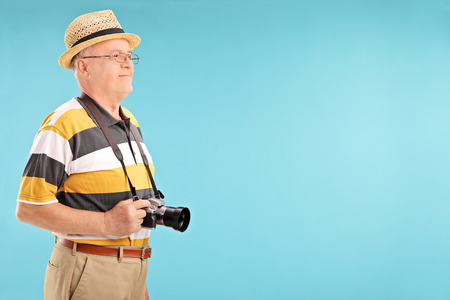 Senior gentleman with camera posing on blue background photo