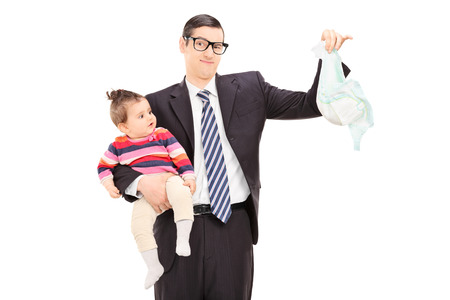 diaper: Young father holding a baby and a dirty diaper isolated on white background