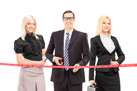 Business people cutting a red tape isolated on white background photo