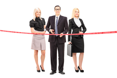 Full length portrait of a business team cutting a red tape isolated on white background photo