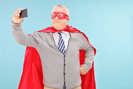 Mature man in superhero costume taking selfie on blue background photo