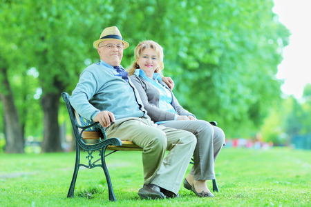 Elderly couple relaxing in park seated on wooden bench photo