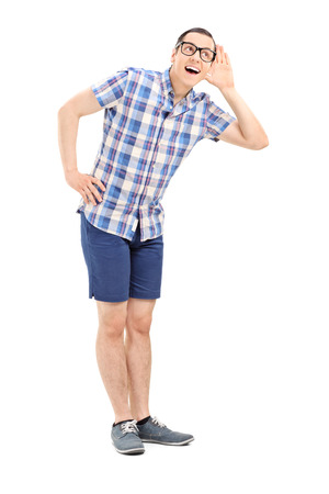 Full length portrait of a young man trying to hear something isolated photo