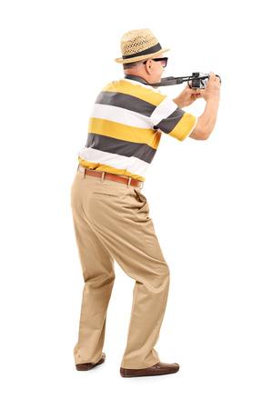 Turista masculino de tomar una foto con la cámara aislada