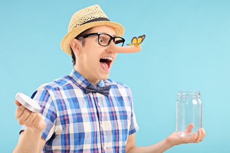 Man trapping a butterfly in a jar on blue photo