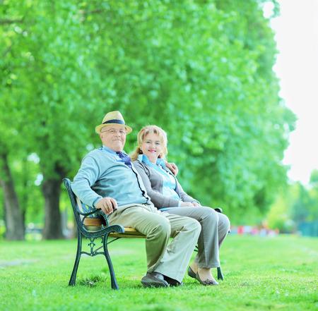 banc de parc: Couple d'âge mûr posant dans le parc assis sur le banc tourné avec bascule et décentrement lentille