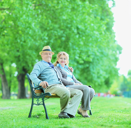 park bench: Mature couple posing in park seated on bench shot with tilt and shift lens Stock Photo