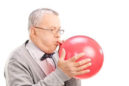 Mature man blowing up a balloon isolated