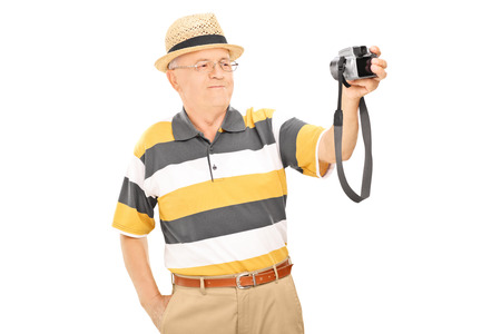 casua: Mature man taking picture of himself with camera isolated  Stock Photo
