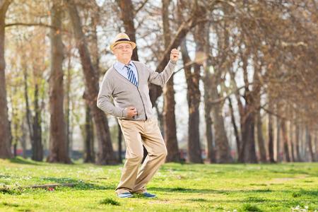 overjoyed: Overjoyed senior playing air guitar in park