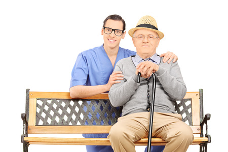 Medical professional and senior sitting on bench isolated on white background photo