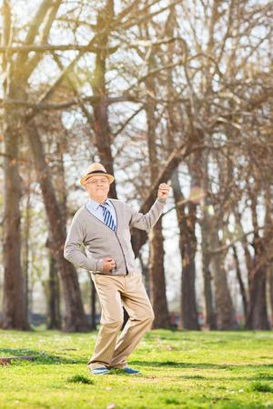 air guitar: Senior gentleman dancing out of joy outdoors