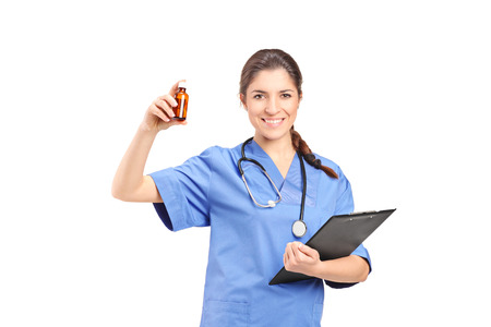 Female doctor holding a bottle of medications and a clipboard isolated on white background photo