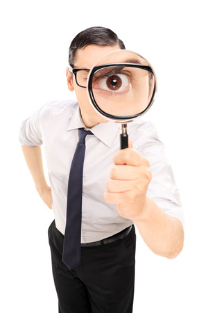 inspecting: Man looking through a magnifying glass isolated on white background Stock Photo
