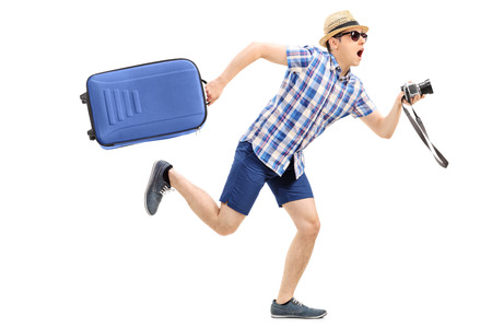 running late: Male tourist rushing with his baggage and camera in hand isolated on white background Stock Photo
