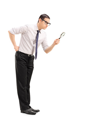 magnifying glass man: Serious man looking through a magnifying glass isolated on white background