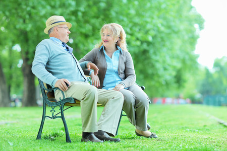 Elderly couple relaxing on a bench outdoors photo