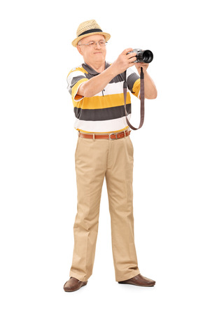 Full length portrait of a mature man taking a picture with camera isolated on white background photo