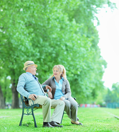 Mature couple talking seated on bench in park shot with tilt and shift lens photo
