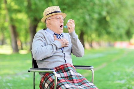 Senior homme d'étouffement dans le parc et titulaire d'un inhalateur