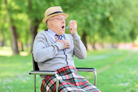 difficulties: Senior man choking in park and holding an inhaler Stock Photo