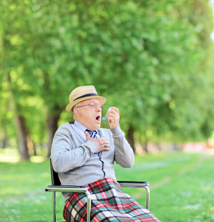 terrified: Senior man having an asthma attack in park shot with tilt and shift lens Stock Photo