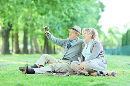 Mature couple taking selfie on a picnic outdoors photo