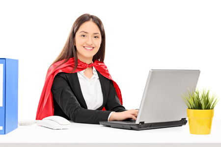 Woman in hero costume working on laptop isolated on white background photo