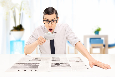 baffled: Surprised man reading the news with scrutiny in an office Stock Photo