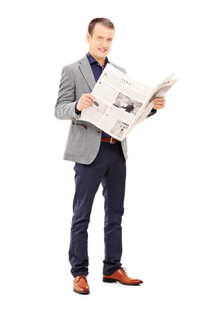 Full length portrait of a young man holding a newspaper and looking at camera isolated on white background