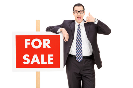 Male realtor standing by a for sale sign isolated on white background photo