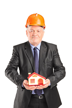 Mature engineer holding a small model house isolated on white background photo
