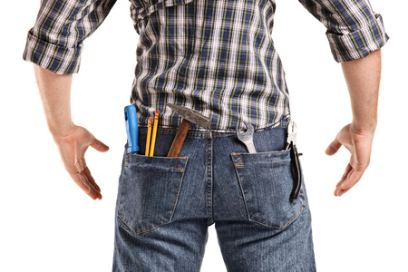 Rear view, studio shot of a man with tools in the pockets of his jeans isolated on white background photo