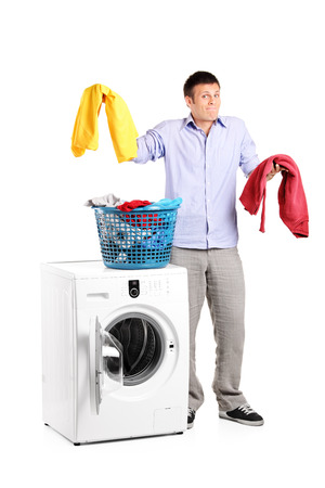 Studio shot of a man wondering how to do the laundry isolated on white background photo