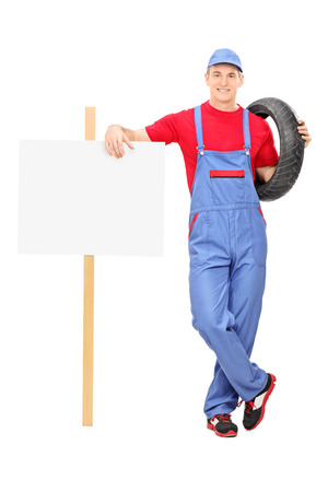 Full length portrait of a male mechanic standing next to a blank sign isolated on white background photo