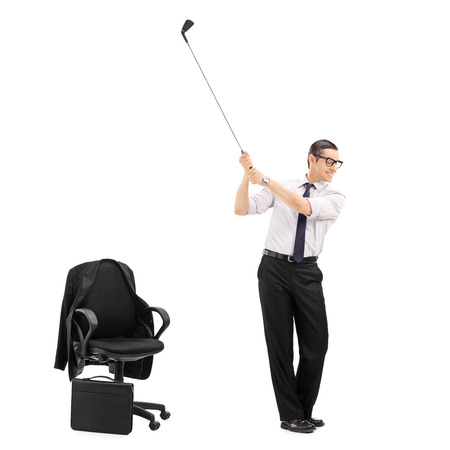tilt shift: Businessman swinging a golf bat with an office chair beside him isolated on white background shot with tilt and shift lens
