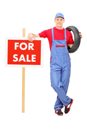 jumpsuit: Full length portrait of a male mechanic standing by a for sale sign isolated on white background