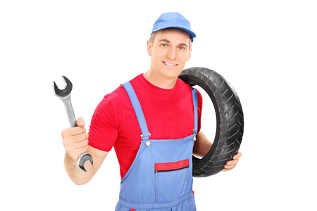 Male mechanic holding a wrench and a tire isolated on white background photo