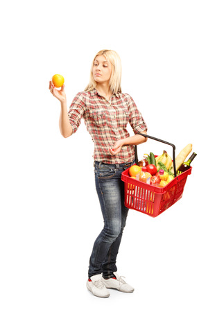 checking ingredients: Full length portrait of a young woman holding a basket full of groceries isolated on white background