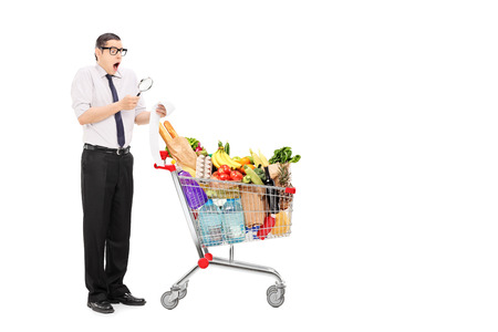 inspecting: Full length portrait of a shocked man examining the shopping bill