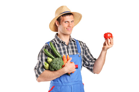 jumpsuit: Gardener holding a bunch of vegetables and a single tomato isolated on white background