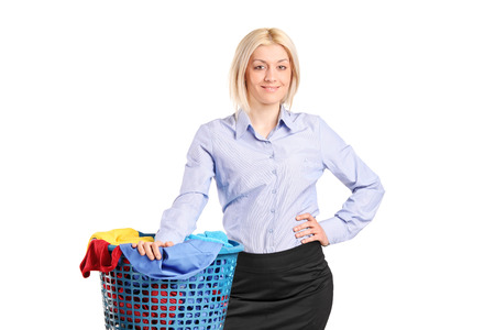 Woman standing by a laundry basket full of clothes isolated on white background photo