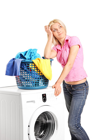 lean machine: Bored woman standing by a washing machine isolated on white background