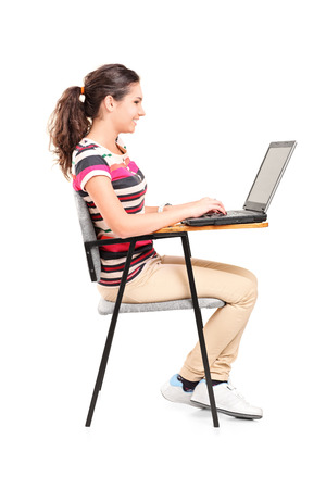 Profile shot of a schoolgirl working on laptop isolated on white background photo