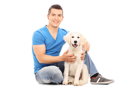man dog: Young man sitting with his dog on the floor isolated on white background