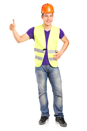 Full length portrait of a male construction worker giving a thumb up isolated on white background photo