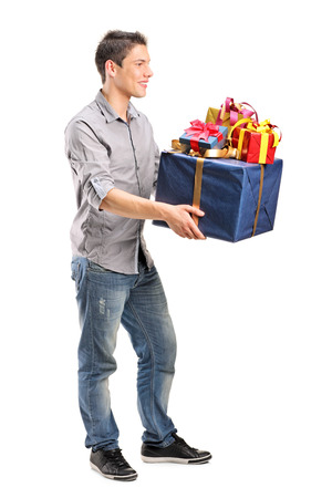 Full length portrait of a young man holding a bunch of presents isolated on white background photo