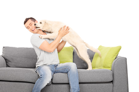 Man playing with a puppy seated on sofa isolated on white background Stock Photo
