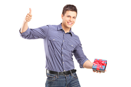 posing  agree: Young man holding a present and giving thumb up isolated on white background Stock Photo
